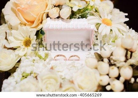 wedding rings on the box with flower