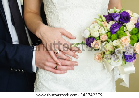Wedding rings on the hands of the bride and groom. - stock photo
