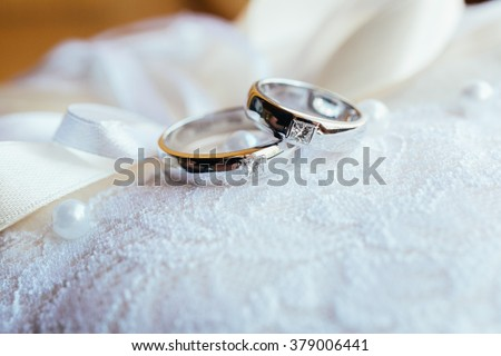 Wedding rings on the lace pillow - stock photo