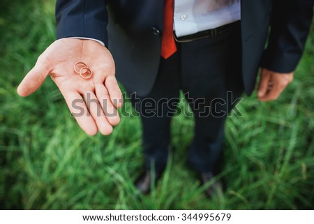 Wedding Rings On The Palm Of The Groom - stock photo