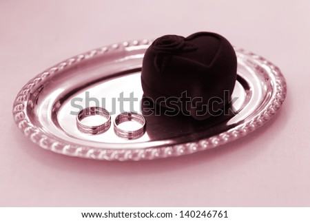 Wedding Rings on the tray colored in red, focused to the rings - stock photo