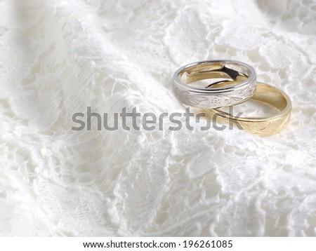 Wedding rings on white lace - stock photo