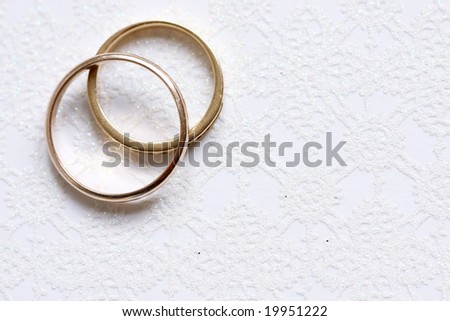 Wedding rings on white paper with floral patern - stock photo