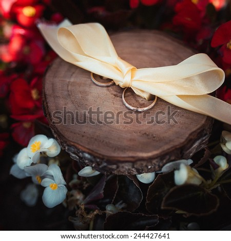 wedding rings on wood surface with flowers - stock photo