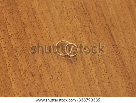 Wedding rings on wooden table. - stock photo