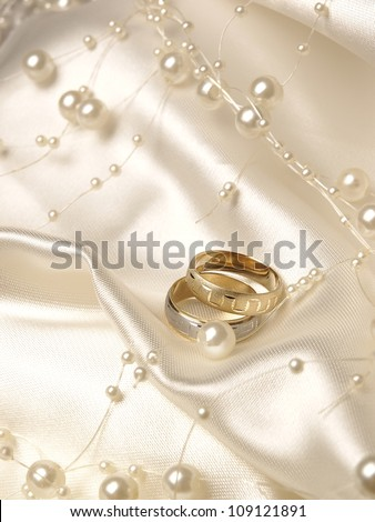 Wedding rings, pearls and silk