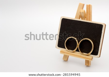 Wedding rings placed on a chalkboard - stock photo