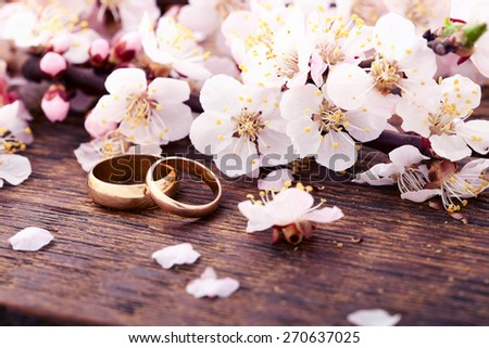 Wedding rings. Spring. Flowering branch with white delicate flowers on wooden surface. Declaration of love, two hearts, couple. Wedding invitation space for text - stock photo
