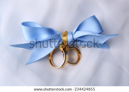 Wedding rings tied with ribbon on light background - stock photo