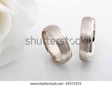 Wedding rings whit white rose. - stock photo