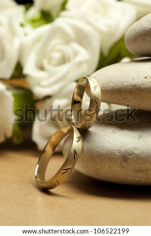 Wedding rings, white roses and pebble stones - stock photo