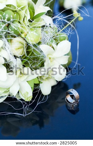 wedding rings with bouquet - stock photo