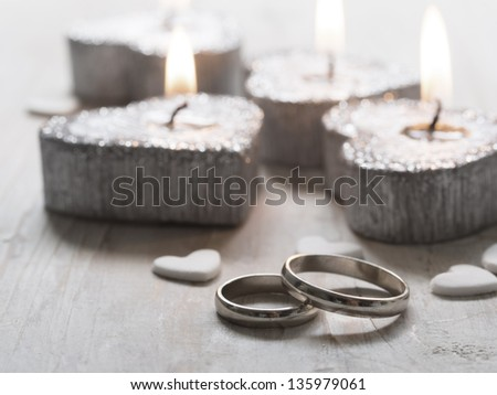 wedding rings with burning candles - stock photo