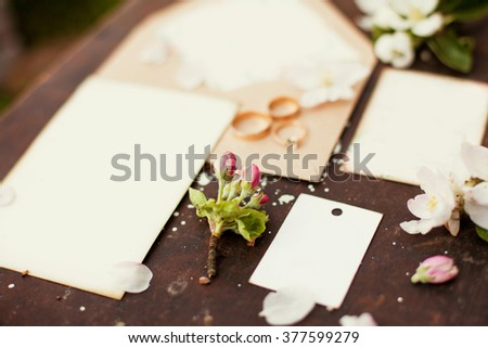 Wedding rings with invitations and flowers - stock photo