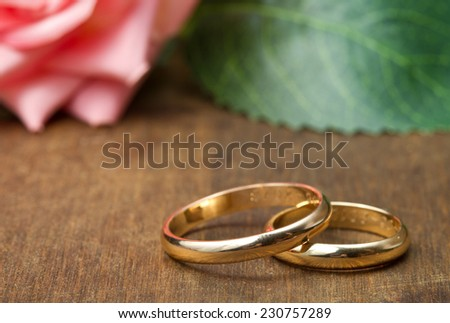 wedding rings with pink roses on wooden background - stock photo