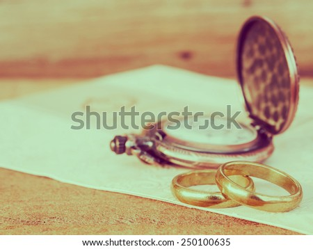 Wedding rings with pocket watch background for wedding or valentines days concept in vintage style. - stock photo