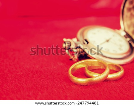 Wedding rings with pocket watch on red  background for wedding or valentines days concept in vintage style. - stock photo