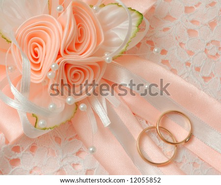 wedding rings with satin roses - stock photo