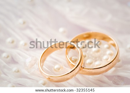 wedding rings with silk and perls - stock photo