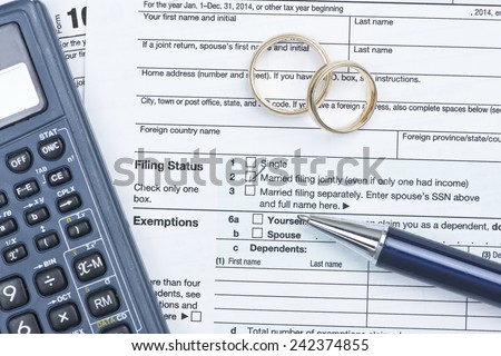 Wedding rings with United States tax form 1040 and pen and calculator.