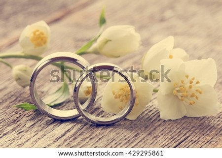 Wedding rings with wild flower on wooden background