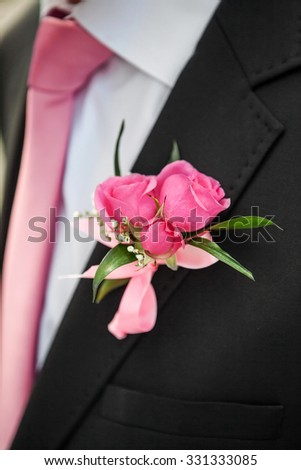 wedding rose boutonniere in groom's tuxedo with rose tie - stock photo
