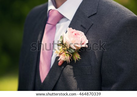 wedding rose boutonniere in groom's tuxedo with rose tie