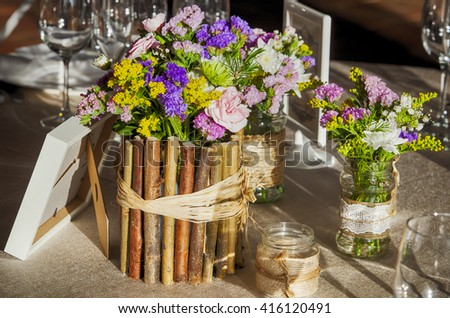 Wedding rustic table full of wild flowers and and country decoration