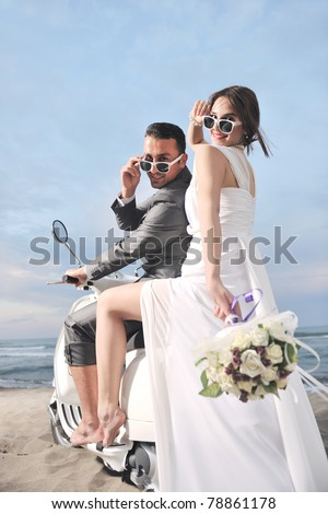 wedding sce of bride and groom just married couple on the beach ride white scooter and have fun