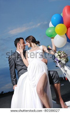 wedding scene of bride and groom just married couple on the beach ride white scooter and have fun - stock photo