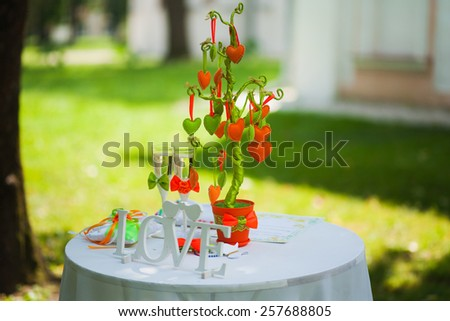 Wedding settings for outdoors celebration. beautiful decorations of tables for wedding reception. green park. no people. tree of hearts - decor for party. wooden word love. two glasses of champagne - stock photo
