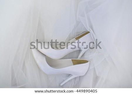Wedding shoes on wedding dress background - stock photo