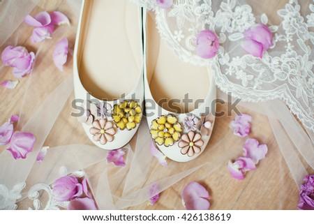 wedding shoes, veil and petals - stock photo