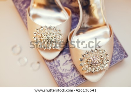 wedding shoes with brooch and wedding rings - stock photo