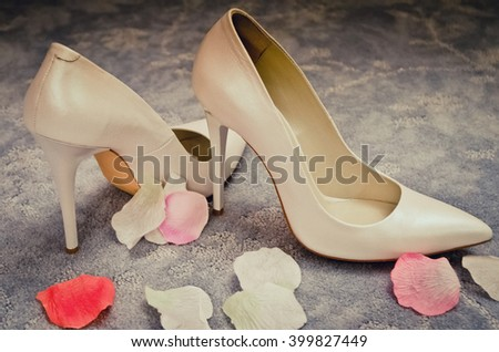 wedding shoes with rose petals - stock photo