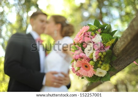 Wedding shot of bride and groom stand in park (focus on bouquet) - stock photo