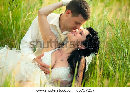 Wedding shot of sexy newly-married couple lie on green grass in field - stock photo