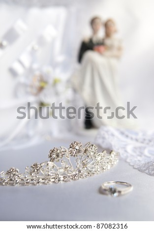 Wedding silver tiara decorated with diamonds. Near the tiara ring is the bride, lace detail dress, wedding ring pillow, bride and groom figurines to wedding cake.