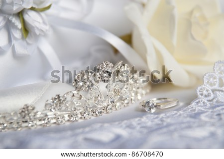 Wedding silver tiara (diadem) decorated with diamonds. Next to the diadem of the other bridal accessories for brides. Ring, the details of clothing and a rose. Wedding macro still life.