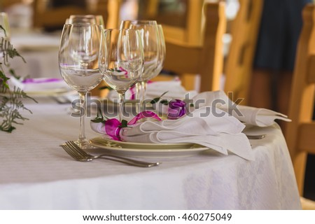 Wedding summer table decoration with flowers. White plates, forks, knifes and wineglasses