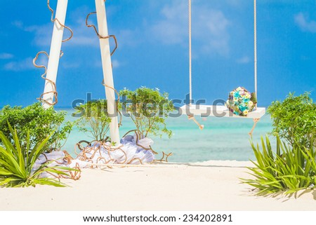 wedding swing decorated with flowers on tropical sand beach, outdoor beach wedding setup - stock photo