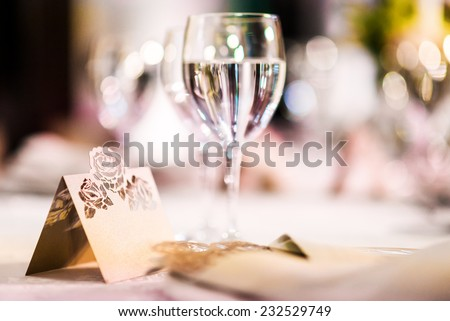 Wedding table. Close-up of wine glass and name card   - stock photo