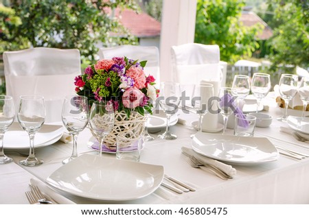 Wedding table decor with colorful flowers and plates