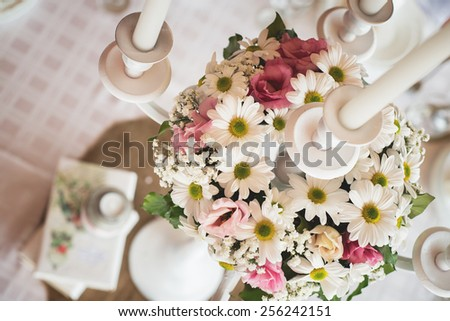Wedding table decoration at restaurant. Shallow depth of field. Candle holder with flowers. - stock photo