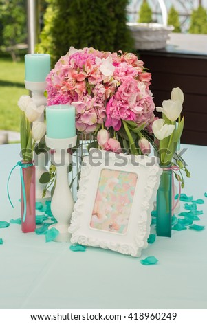 Wedding Table Decoration in mint and pink colors. Table set for a wedding dinner. Beautiful flowers on table in wedding day - stock photo