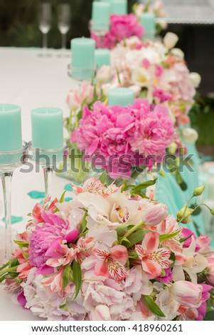 Wedding Table Decoration in mint and pink colors. Table set for a wedding dinner. Beautiful flowers on table in wedding day