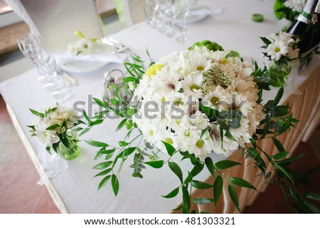 Wedding table decoration in white and green colors. floristry. Fresh mix