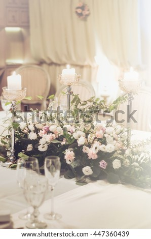 Wedding table set, elegant floristics decoration in banquet restoraunt. Floral composition beige roses flowers with high, elegant candle coasters, glass goblets for wine. Text, free copy space. - stock photo