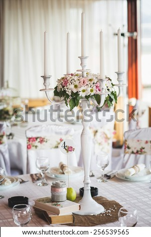 Wedding table setting decoration, candle holder, white candle, flowers. - stock photo