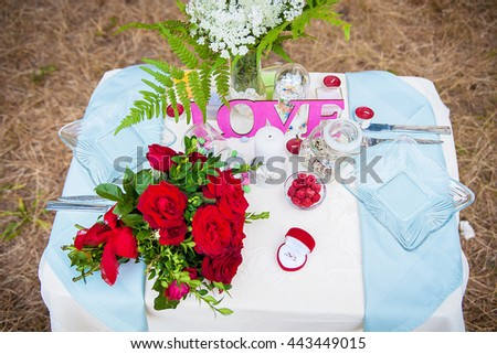 Wedding table setting in nature. Bridal bouquet and ring